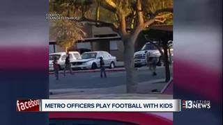 Officers play football with kids in complex